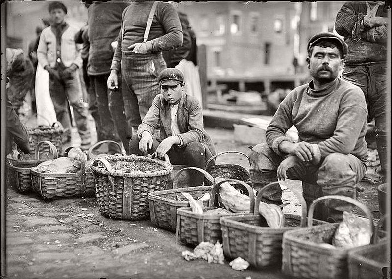 Boy selling fish from a basket in Boston street market, October 1909