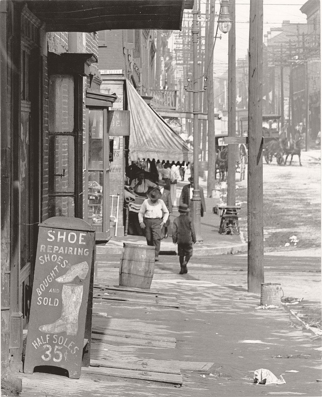 Sidewalk scene on a street in St. Louis, ca. 1900s