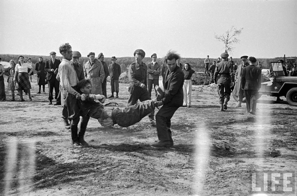 German SS soldier who passed out from carrying corpses being carried by two others at the Bergen Belsen concentration camp.
