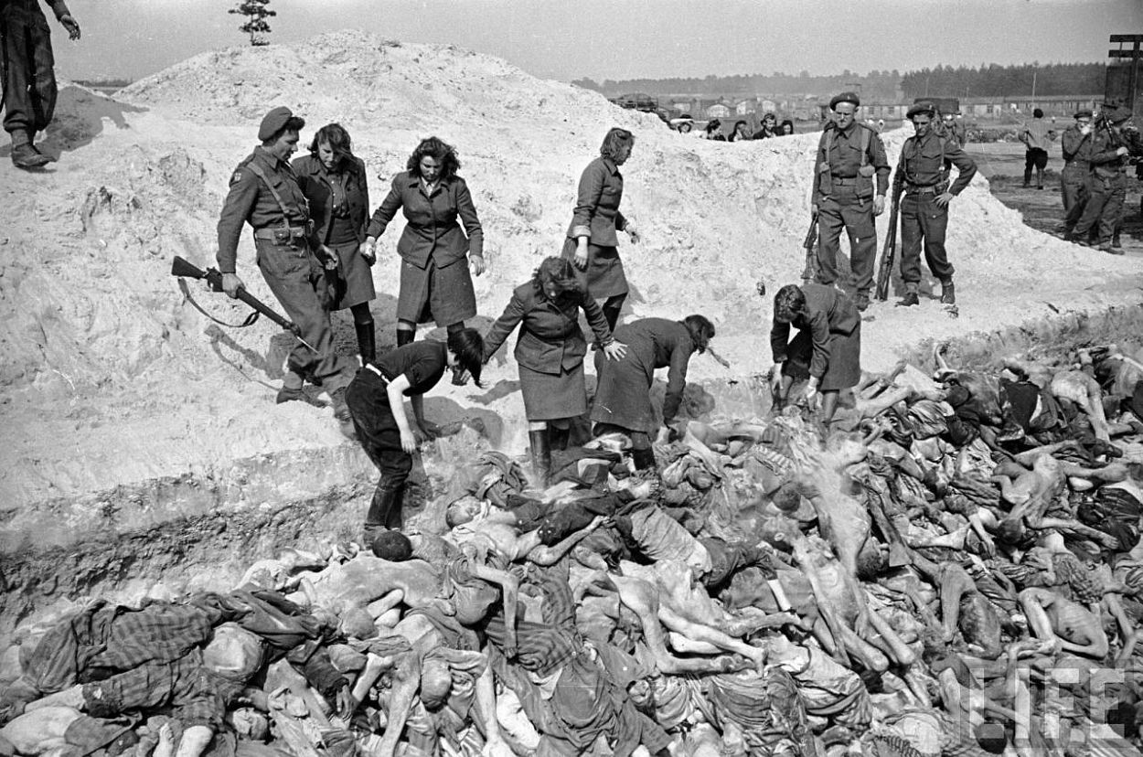 Female SS soldiers filling mass grave w. corpses while under guard by British soldiers at the Bergen Belsen concentration camp.