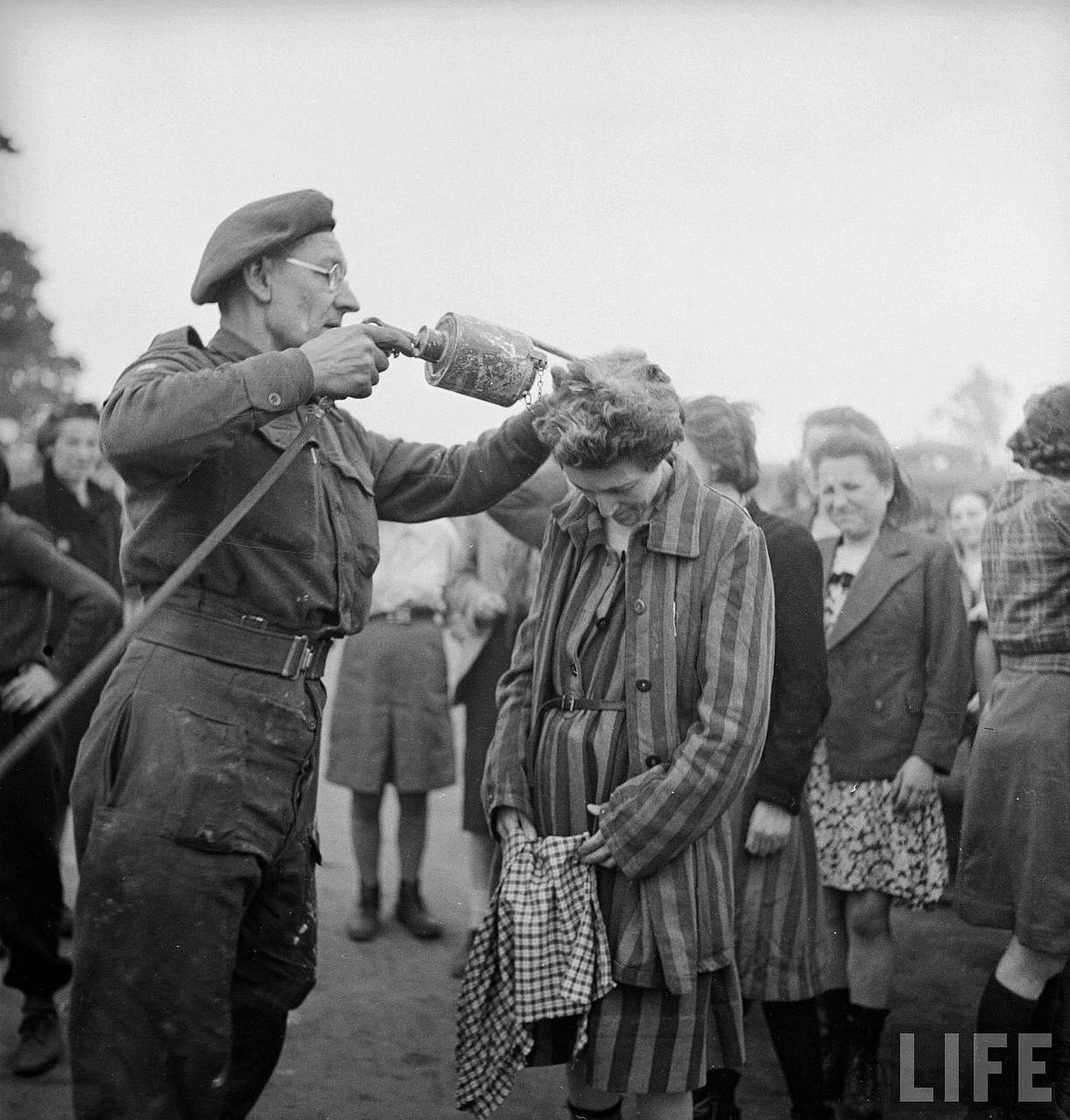 British doctor using DDT while delousing newly freed female prisoners at the Bergen Belsen concentration camp.