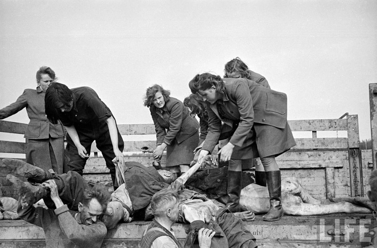 Female German camp guards being forced to unload truck full of the bodies of deceased priosners at the Bergen Belsen concentration camp.