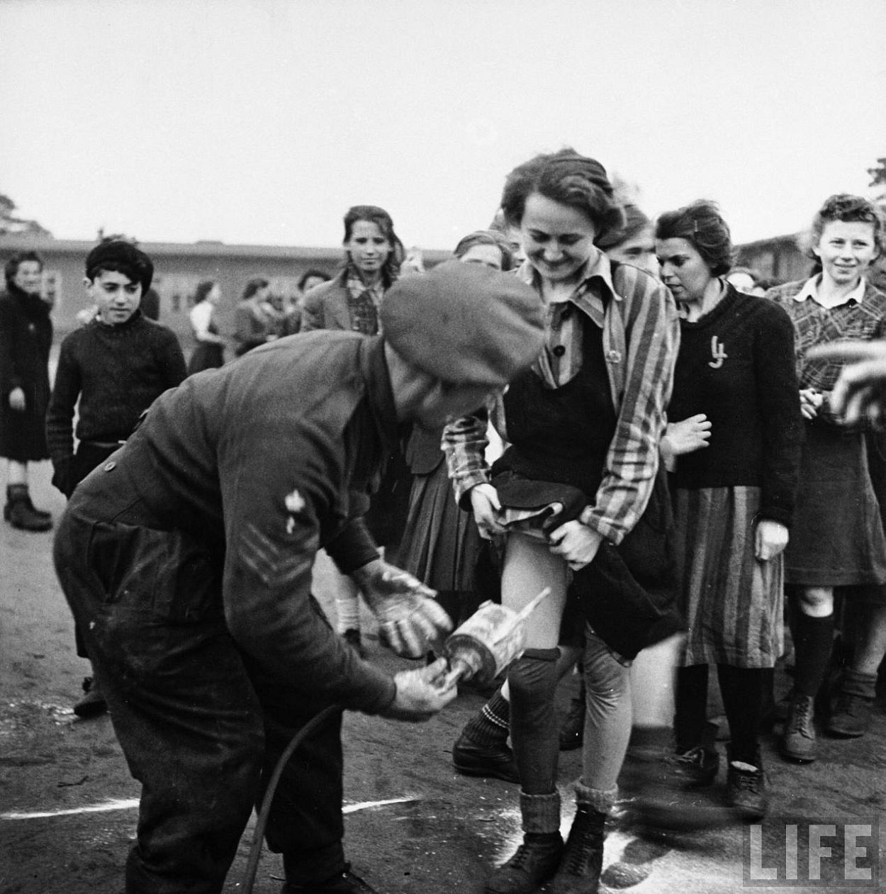 British doctor administers delousing treatment of DDT up the skirt of an embarrased looking female prisoner who is among the 60,000 prisoners just released from Bergen Belsen concentration camp after its liberation by Allied forces.