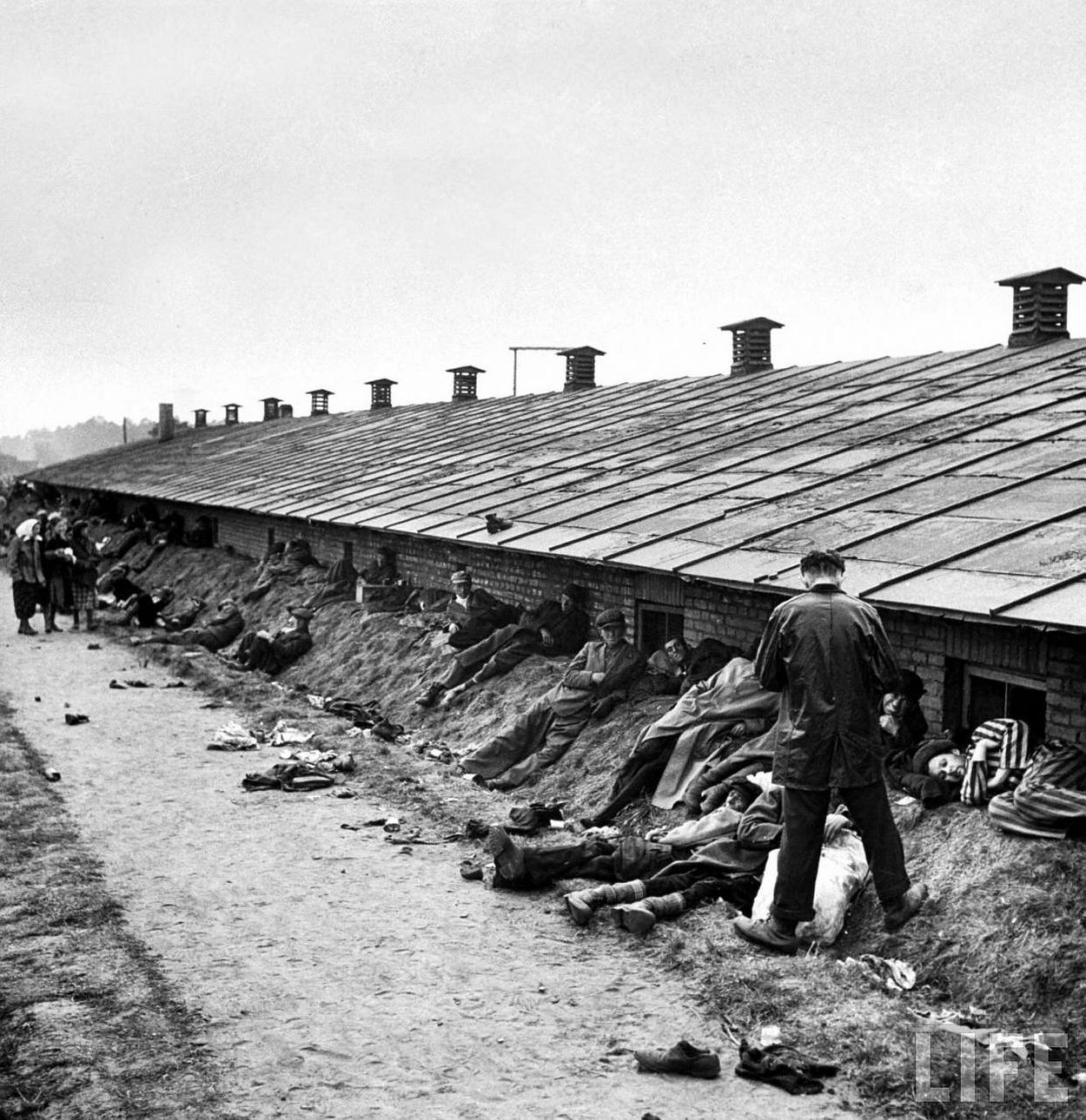 Weak and dying prisoners stretch out on dirt bank behind Bergen Belsen barracks after the concentration camp was liberated by Allied troops.