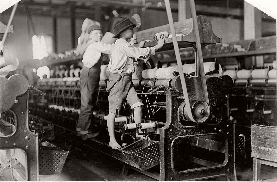 Boys climb up on the spinning frame to mend the broken threads and put back the empty bobbins, Macon, Georgia, 19 january 1909