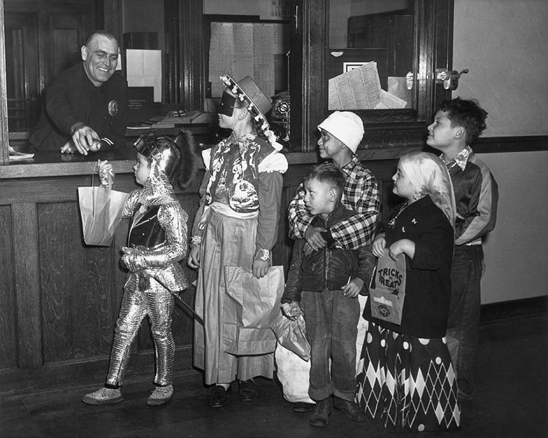 A group of children wearing Halloween costumes wait in a trick-or-treat line to receive apples from an officer at a police precinct, circa 1960. (American Stock / Getty Images)