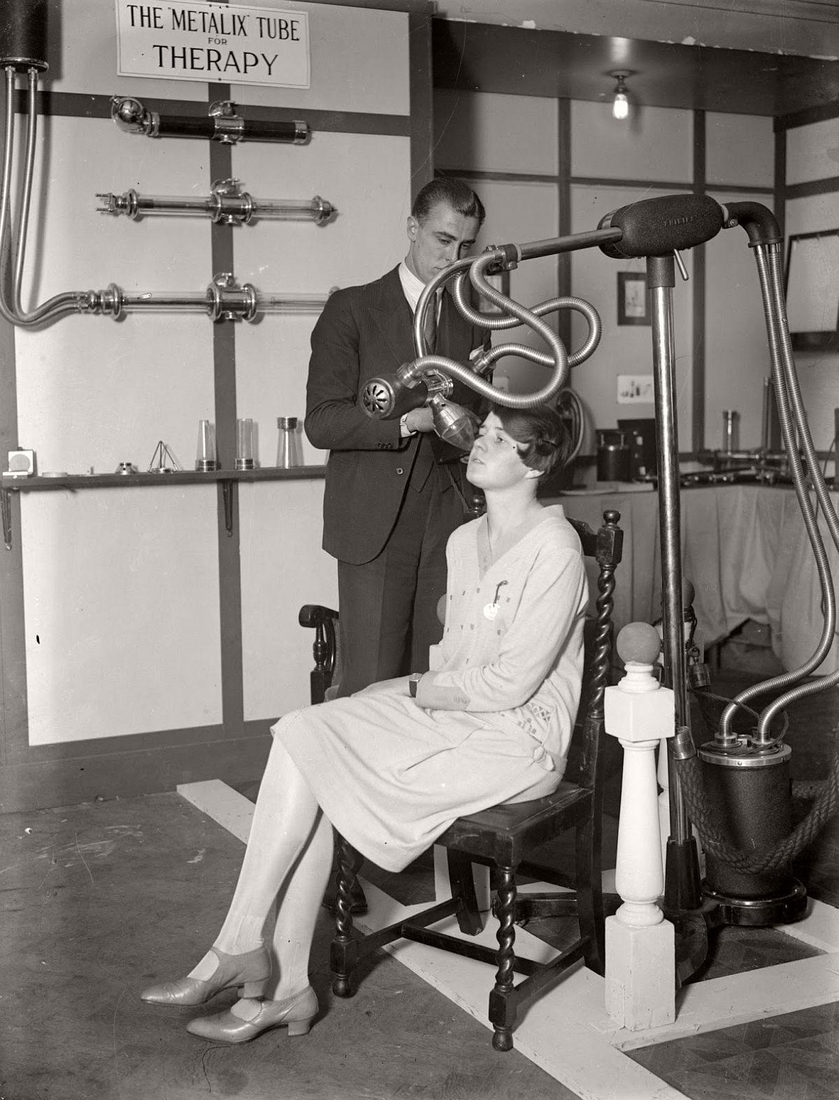 A man and a woman demonstrating medical equipment at a X-ray exhibition, beside a sign reading 'The Metalix Tube for Therapy,' 1928. (Puttnam—Getty Images)
