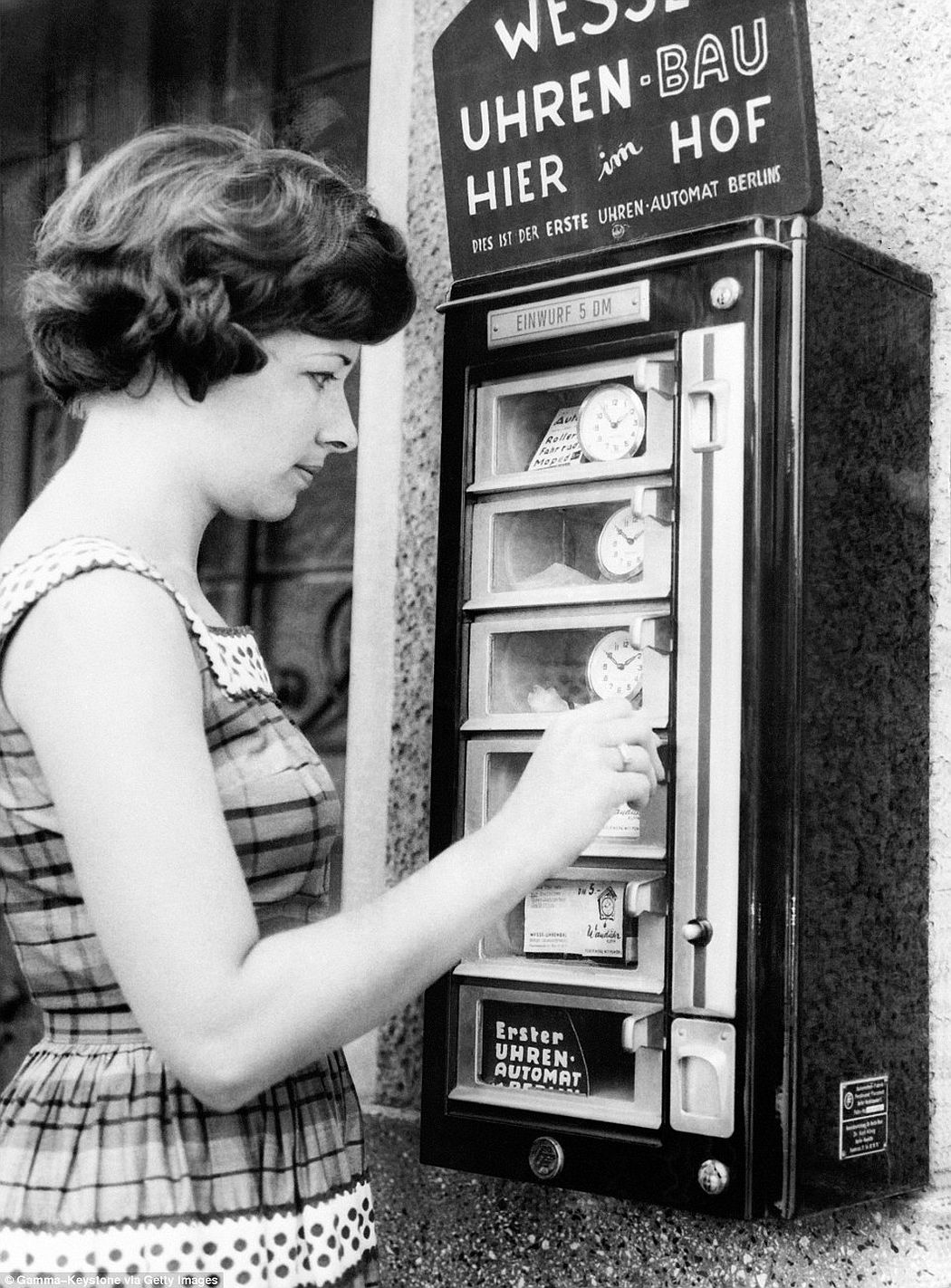 A woman in Berlin, Germany uses a coin-operated device to buy a clock, ca. 1960s.