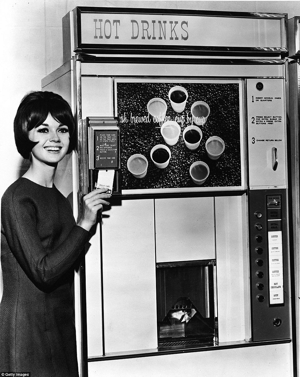 This woman is now able to use a credit card to pay for one of a selection of coffees from this self-serve machine, ca. 1960s.