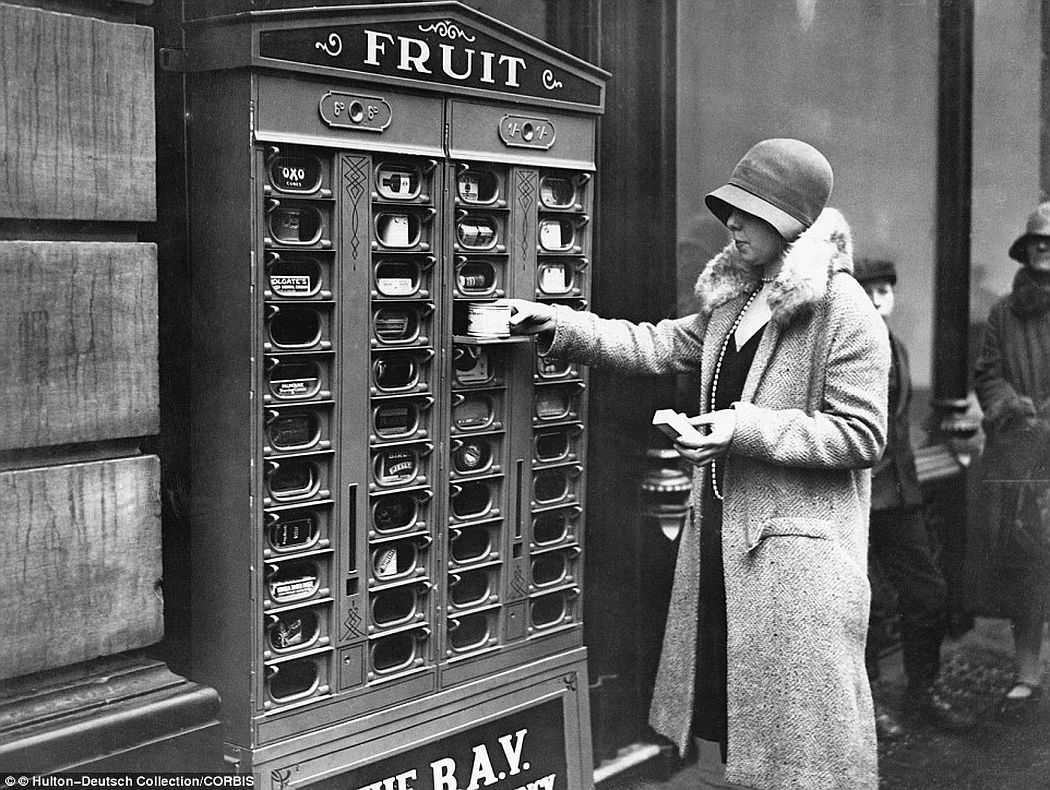 A woman in London is able to continue her grocery shop thanks to a vending machine which says it dispenses fruit but seems to offer kitchen cupboard essentials such as Oxo cubes, tins of food, matches and Colgate products, 1920.