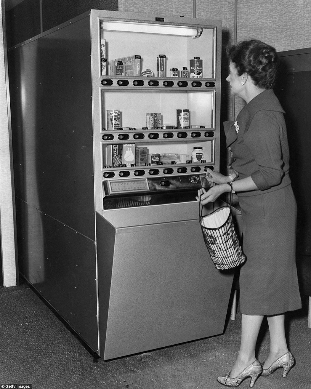 Shoppers could pick up household essentials from this machine. Goods available include Heinz Spaghetti and vegetable soup, Tetley tea, Sugar Puffs, Fray Bentos, Oxo Cubes, soup, light bulbs, mayonnaise and cocoa - all of which could be placed in housewives' own bags, ca. 1960s.