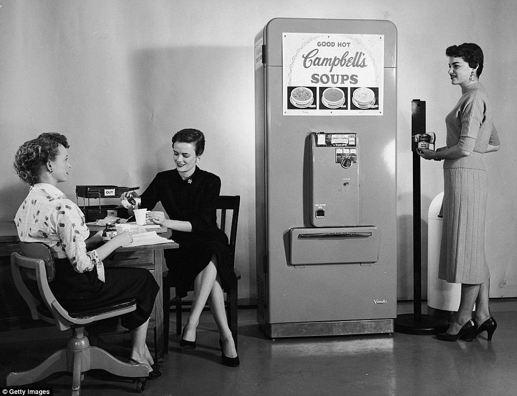 Three women enjoy soup from a Campbell's Soup vending machine in their office, one of the woman opens a can of soup using another nifty gadget, a floor-mounted can opener, ca. 1950s.