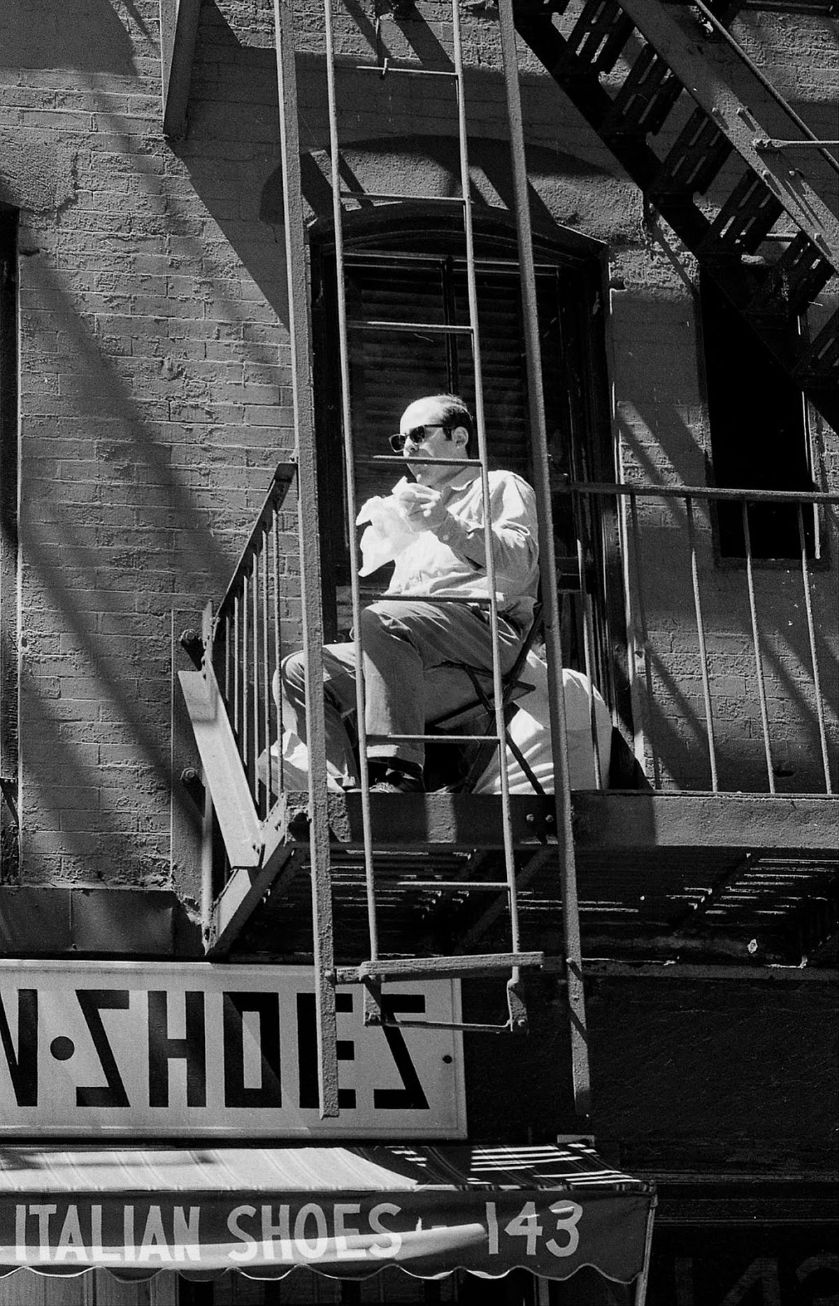 A Little Italy resident watches the production while eating lunch on his fire escape.