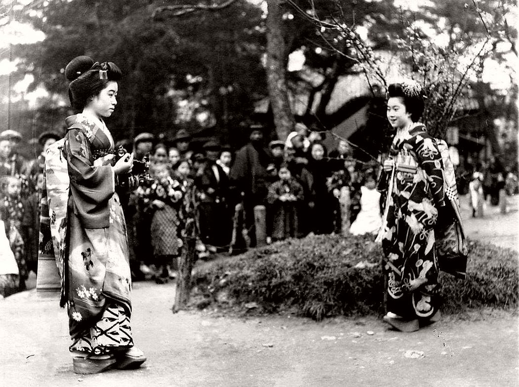 One Maiko taking a photograph of another withe an early Kodak folding camera, ca. 1920s