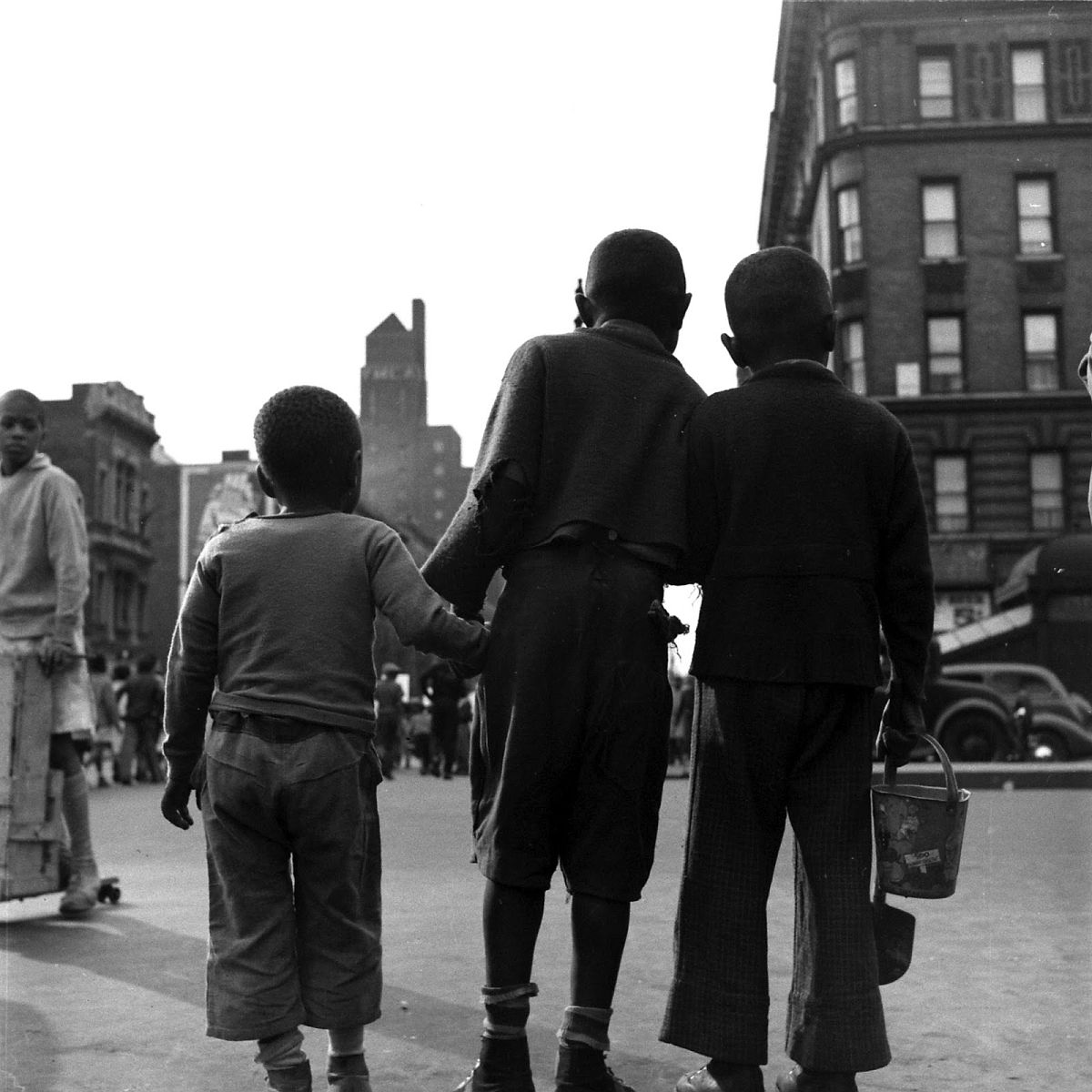 Three young boys hold hands, Harlem, 1938.