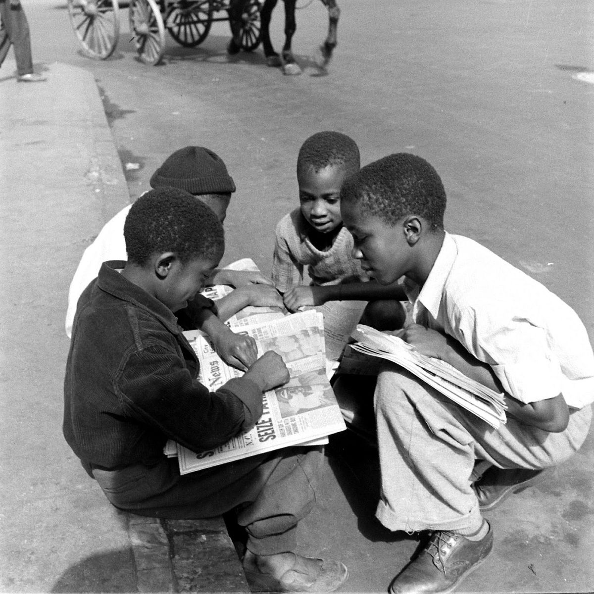 Young boys talk over the day's news, Harlem, 1938.