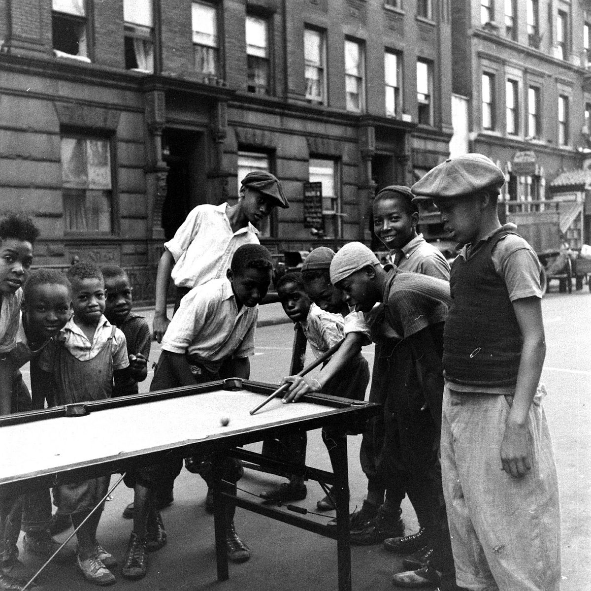 Boys play a makeshift game of pool on a Harlem street, 1938.