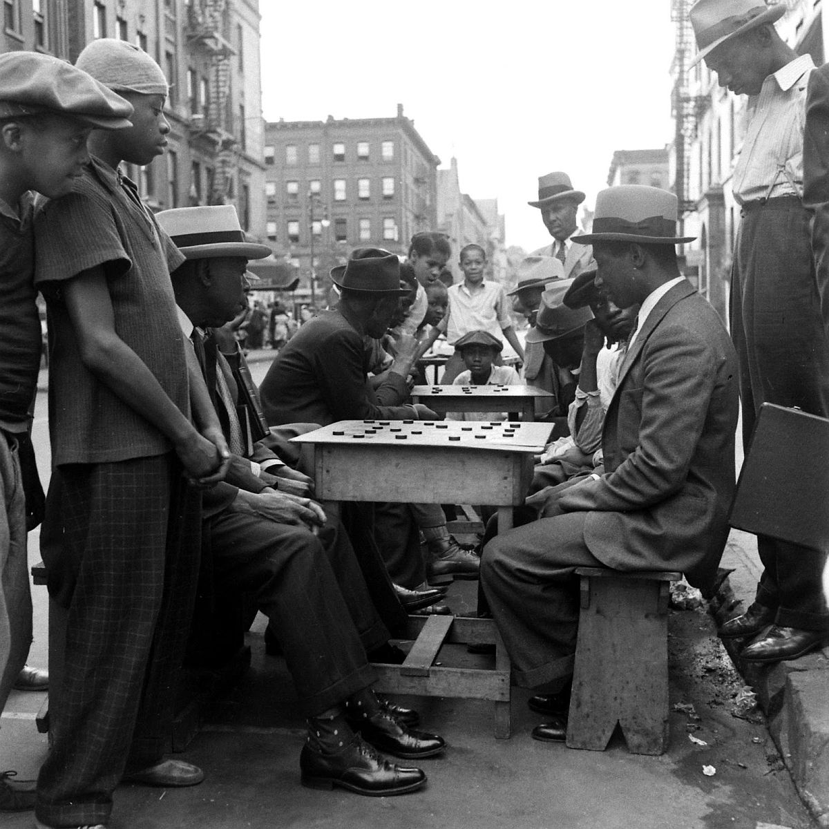 Men face off in stiff competition as boys look on, Harlem, 1938.