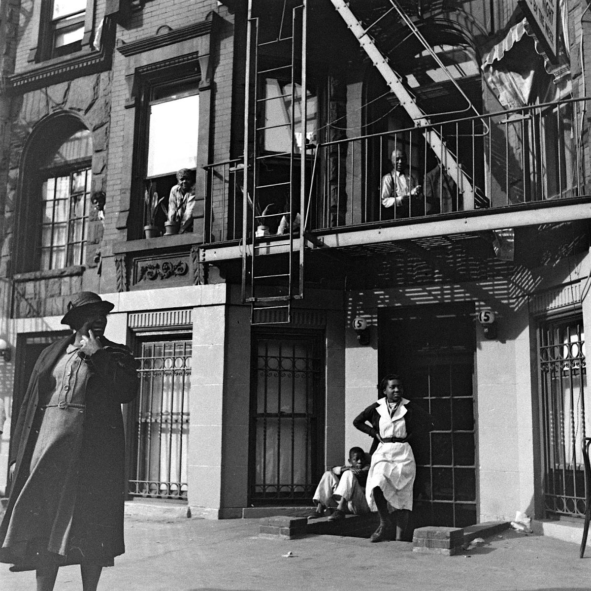 Harlem residents look on at an event taking place just outside the frame, 1938.