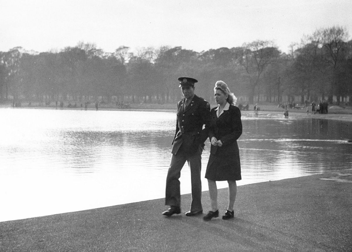 A U.S. officer and his girl walk by the Serpentine, a long and shallow pond in the heart of Hyde park.