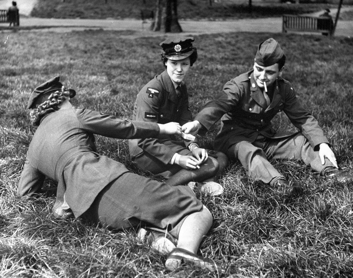 American soldier relaxing in Hyde Park with English girls, 1944.