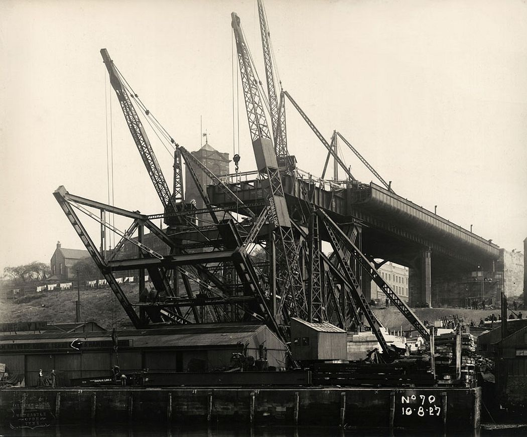 The first sections of steelwork rise over Hillgate Quay, Gateshead, 10 August 1927. Most of the girders in this photograph are part of a temporary cradle used to support the first three sections of the bridge's main arch.