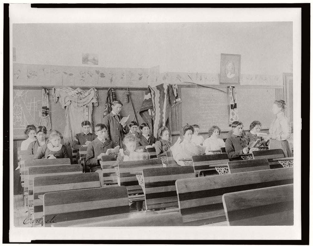 Classroom at the Indian Industrial School, Carlisle, Pennsylvania, showing teacher observing students reading, between 1901 and 1903.