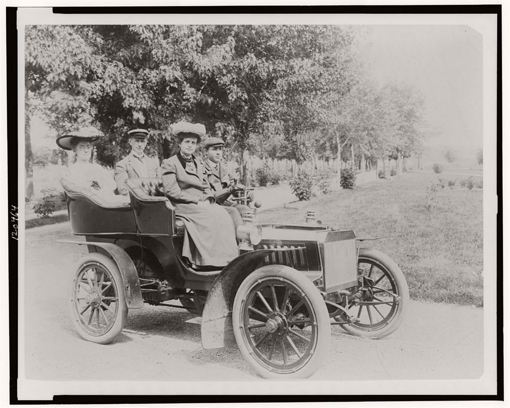 Frances Benjamin Johnston seated with three other people in automobile, between 1890 and 1910.