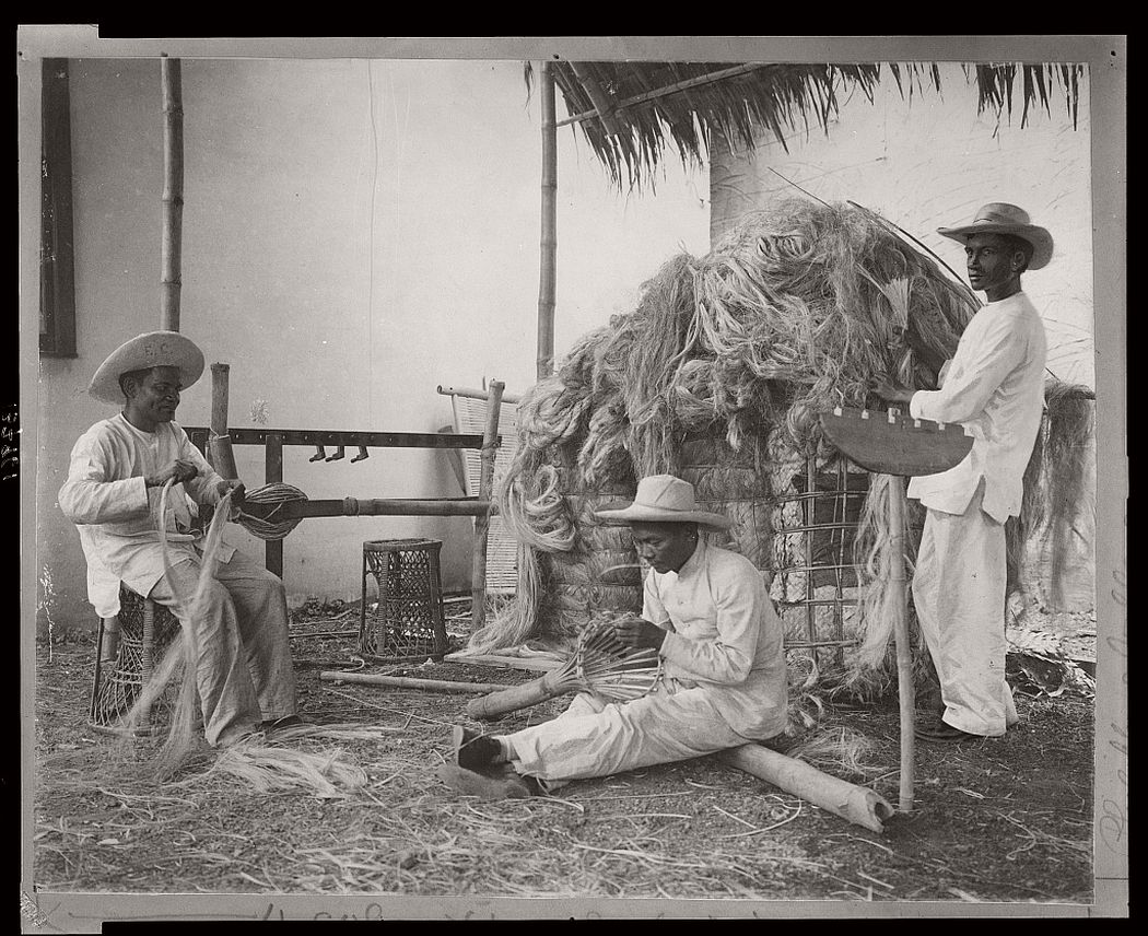 Three Filipino men demonstrating the craft of working with reeds at the Pan-American Exposition, Buffalo, New York, 1901.