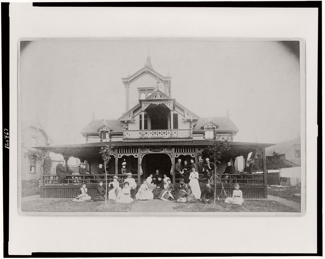 Frances Benjamin Johnston and family on porch and in front of house, between 1890 and 1910.