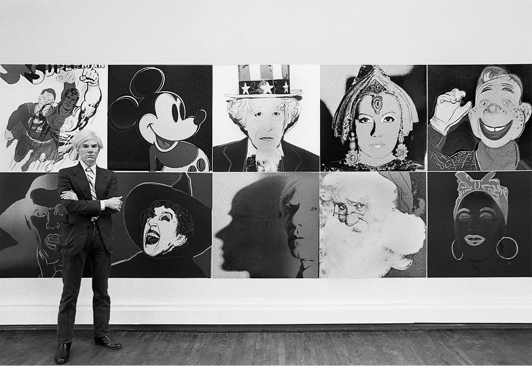 Andy Warhol standing in front of the installation of the Myths at the Robert Feldman Gallery in New York City (1981). Photo: Robert Levin.