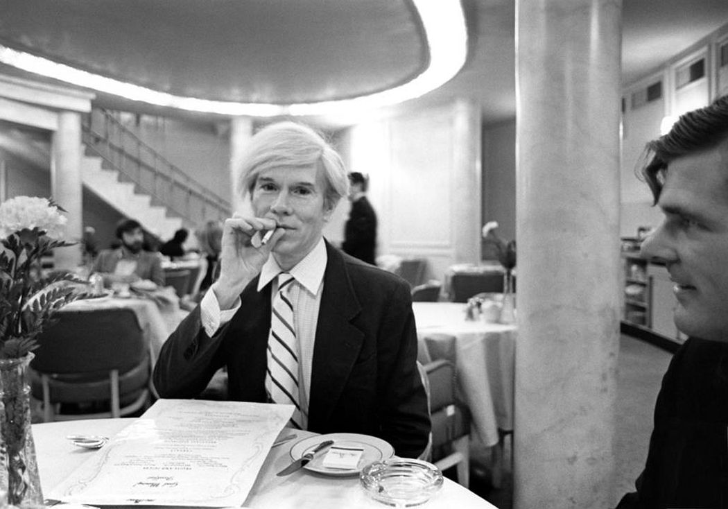 Andy Warhol seated at a table at the Pierre Hotel in New York City (1981). Photo: courtesy Maison Gerard.