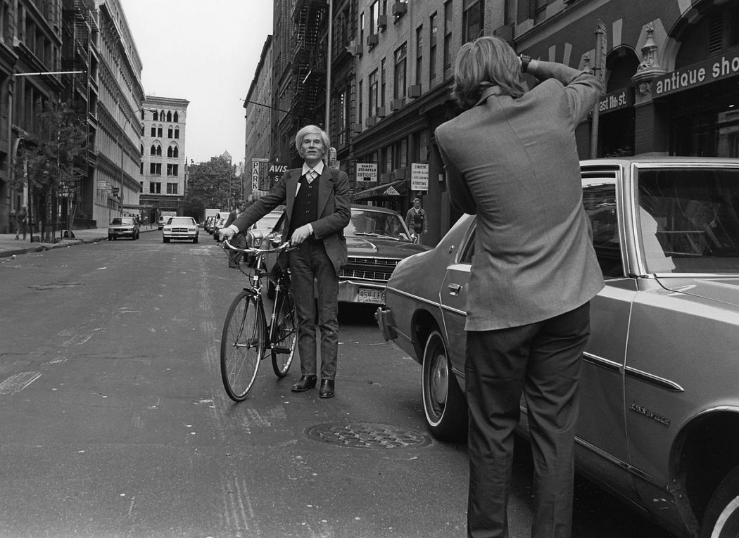 Andy Warhol with a bicycle on East 11th Street in the Village in New York City (1981). Photo: Robert Levin.