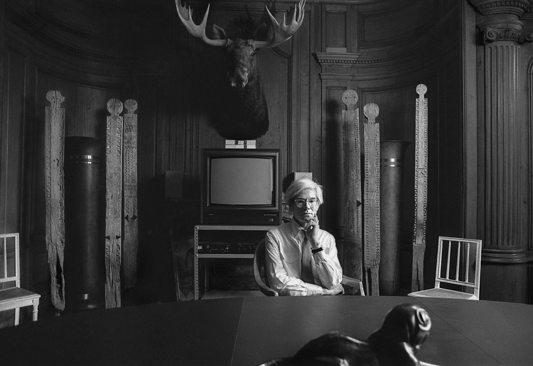 Andy seated in the conference room at the Factory with totems, VCR Television, and moose head taxidermy mounted on the wall (1981). Photo: Robert Levin.