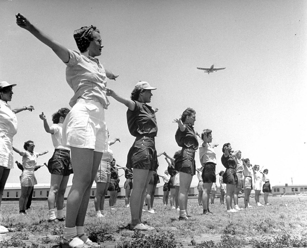 """Arms to the side-raise:"" snaps brisk command of an Army officer as a section of girl pilots begin their daily calisthenics drill, while overhead a primary trainer circles for attitude..."