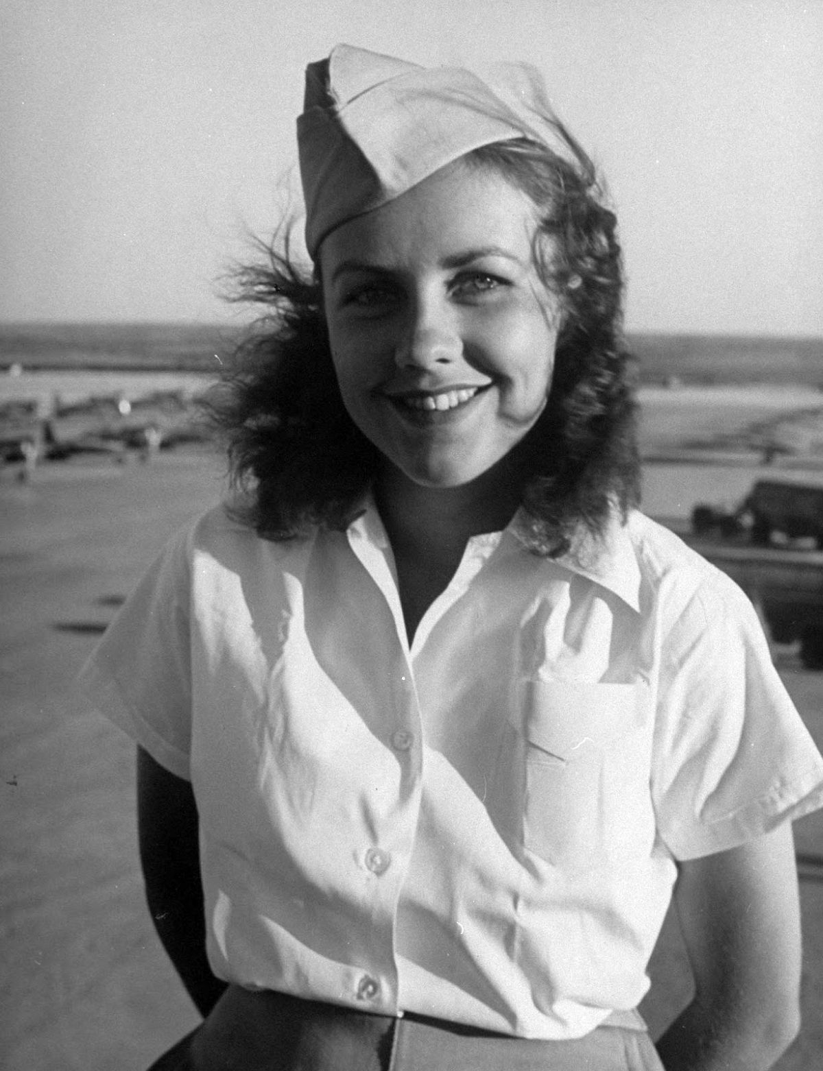 In official dress uniform of white blouse, tan slacks and overseas cap, Shirley Slade smiles as her hair ruffles in Texas wind, free from the pigtail anchoring it has in LIFE's cover picture. The girls wear dress slacks for drill demonstrations and at graduation ceremony.