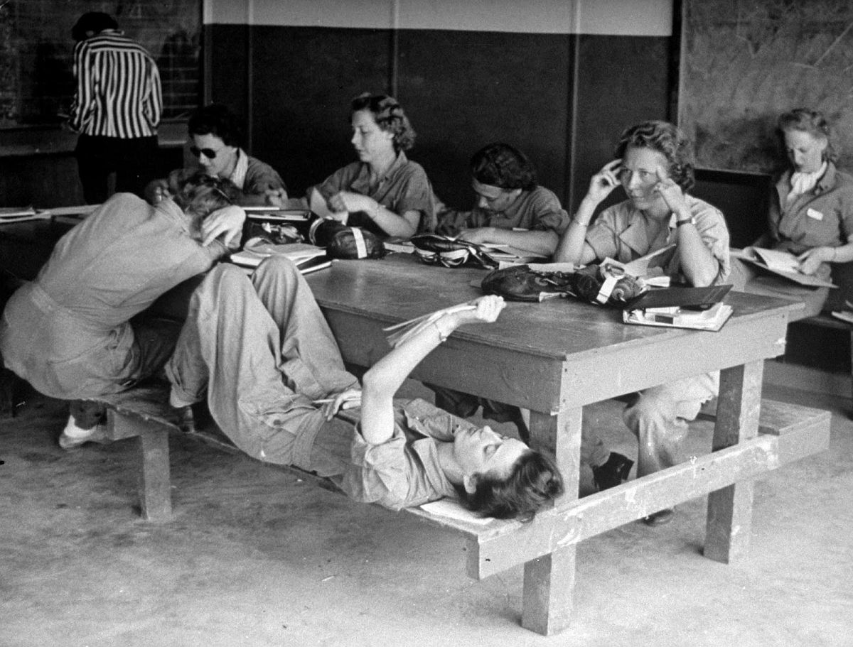 In primary ready room, studious girls memorize the Morse code until the whir of a returning PT flight is heard. Then they get parachutes and take over pilots seats themselves.