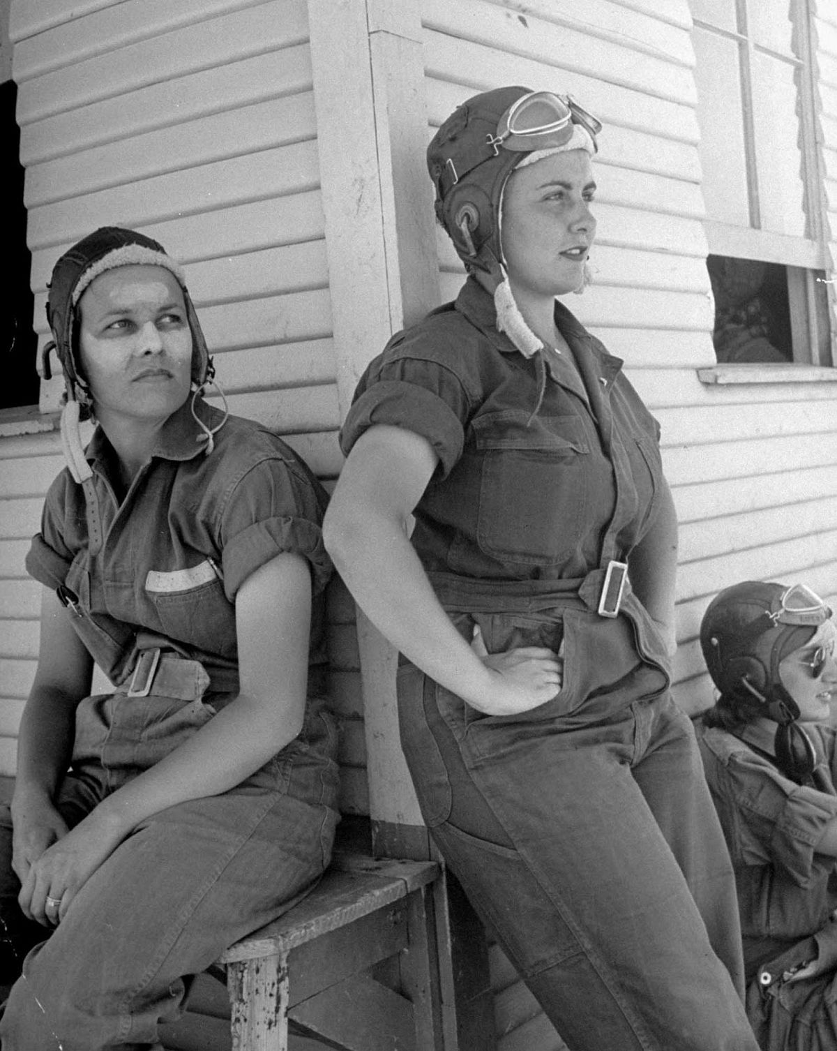"""Sunburned nose and forehead are daubed with protective cream by Rebecca Edwards of Yazoo City, Miss., 22-year-old widow whose husband was killed during duty with the Army Air Forces. Standing next to Rebecca and leaning against the corner of the primary hangar from which both of the girls fly is Lorena Daly of Bakersfield, Calif. They each have on the G.I. coveralls, called """"zoot suits"""" in Avenger Field lingo, that are regulation uniform for all working hours. Though suits are not very glamorous, the girls like their comfort and freedom."""