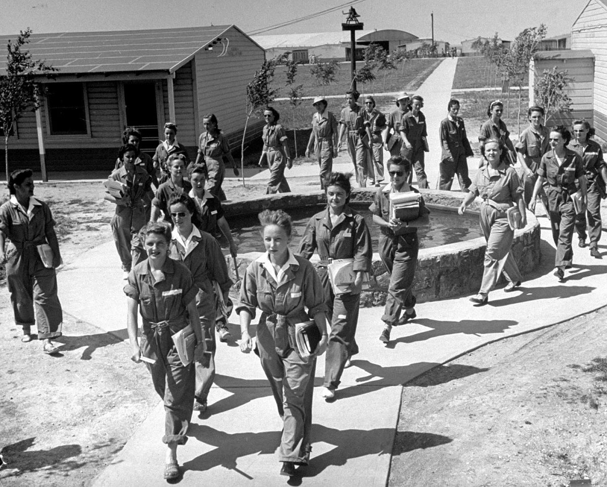 "Marching around wishing well at Avenger Field, girls toss coins for luck if they're due for a flight with an Army pilot. Always the trainees march in formation to the ""Hup, two, three, four!"" of their section leader, going to mess, ground school or flight line."