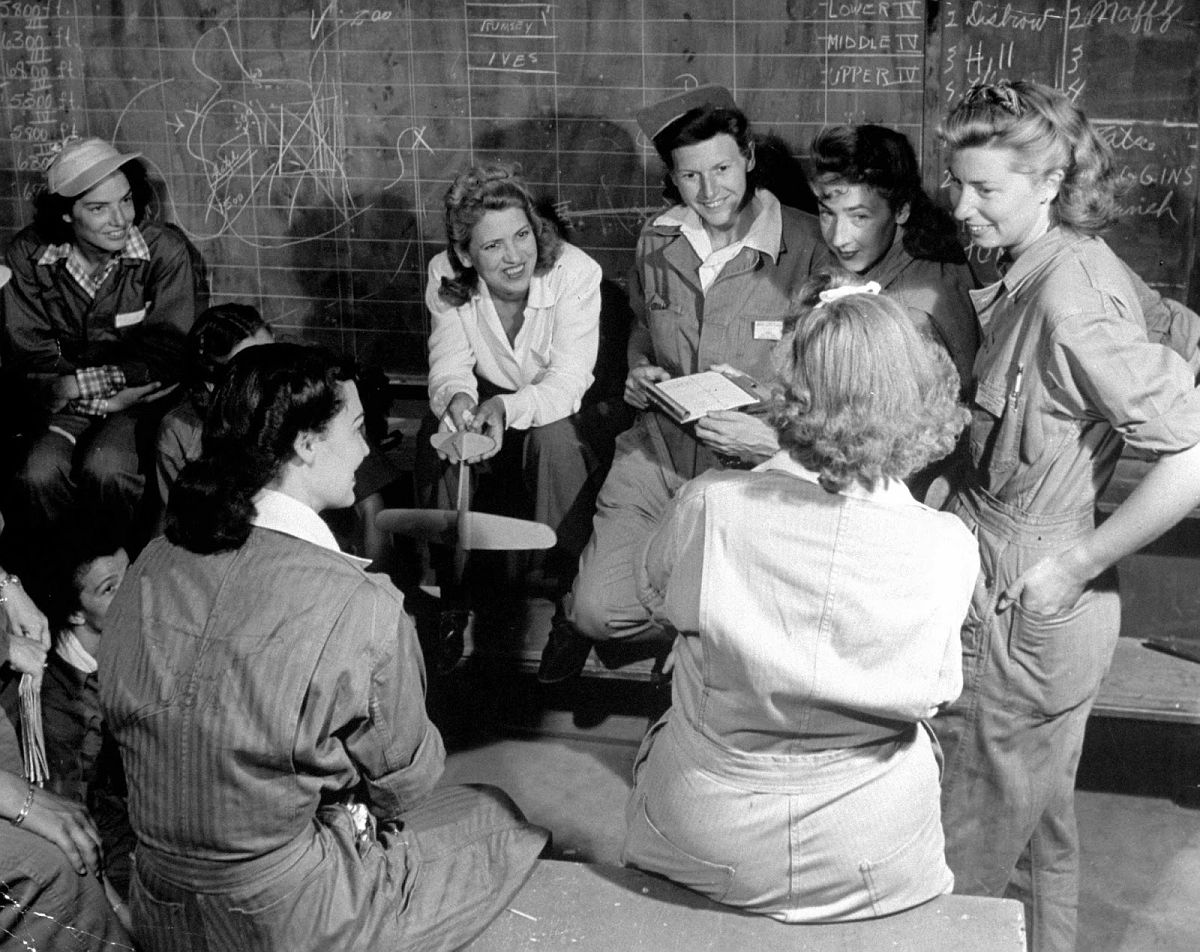Jacqueline Cochran, glamorous speed flier who developed Women's Flying Training Detachment, is center of this group of protogees in flight-line ready room. While girls wait their turn to fly, they question Miss Cochran on her trip to England and other experiences.