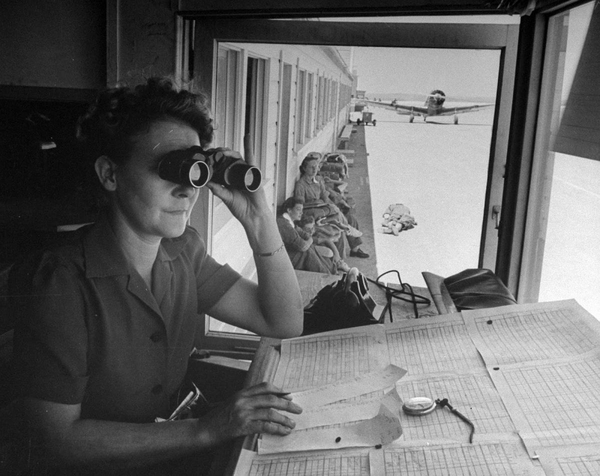 Flight dispatcher looking through binoculars as she watches overflight training traffic of trainee pilots of the Women's Flying Training Detachment at Avenger Field.