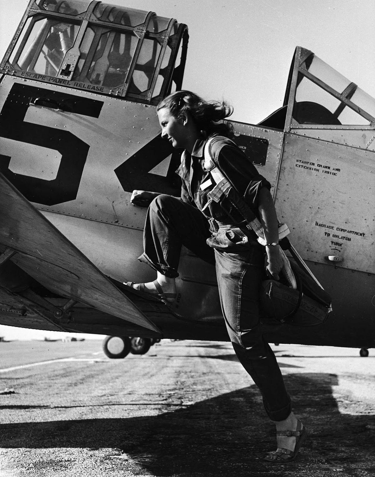 Female pilot of the US Women's Air Force Service posed with her leg up on the wing of an airplane.