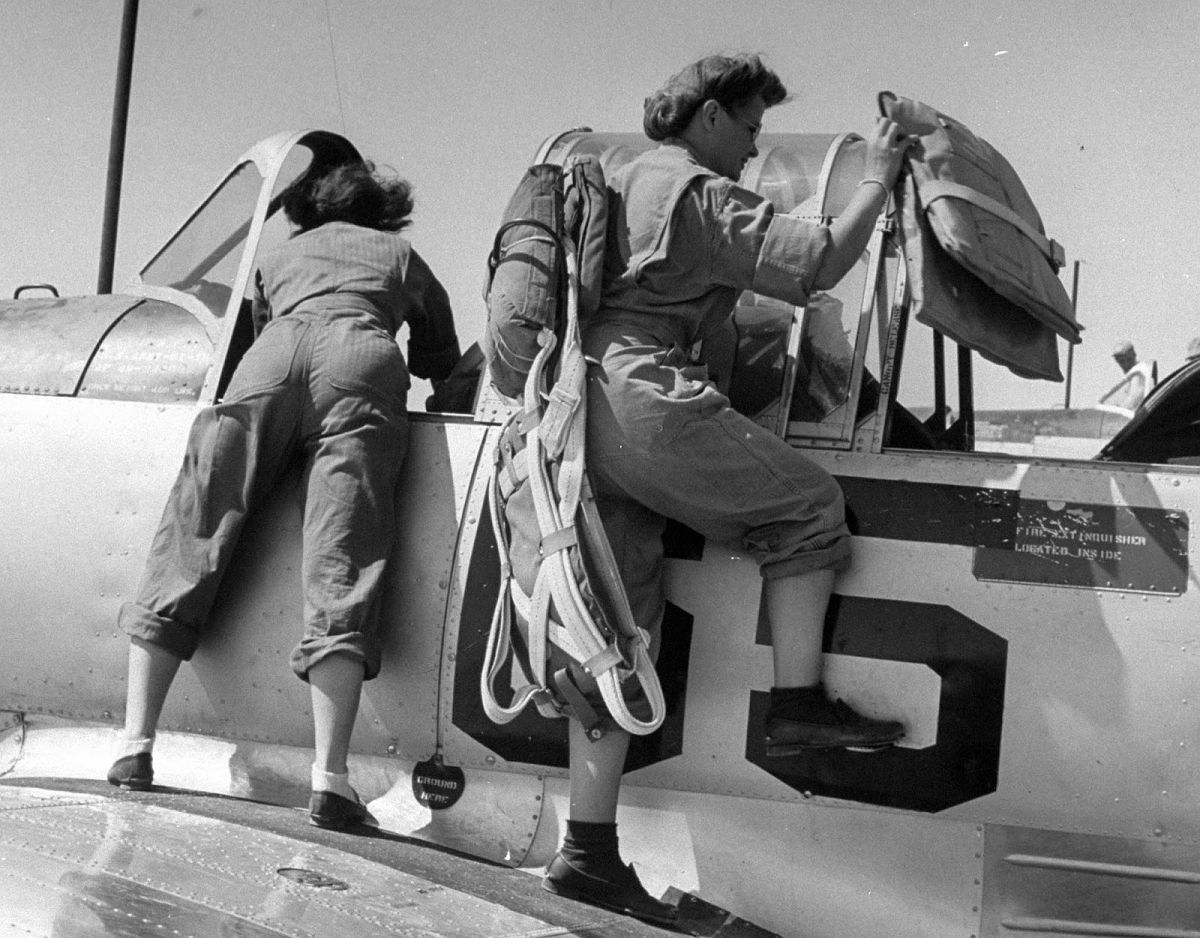 "Short-legged girls stow extra cushions in basic trainer before starting instrument flight, called a ""buddy ride"" because it's always flown in pairs, with one girl checking the other."