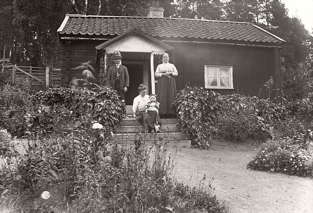 Rakelt, Vrångsjö 1913. Rakelt or Peraklet was a cottage in Vrångsjö manor in Marbäck. The picture shows torparparet Gustav Engdahl (b. 1850) and Augusta Engdahl (b. 1848) and their daughter Esther Engdahl (b. 1888) and her daughter Marta Linnea Ingegerd (b. 1913).