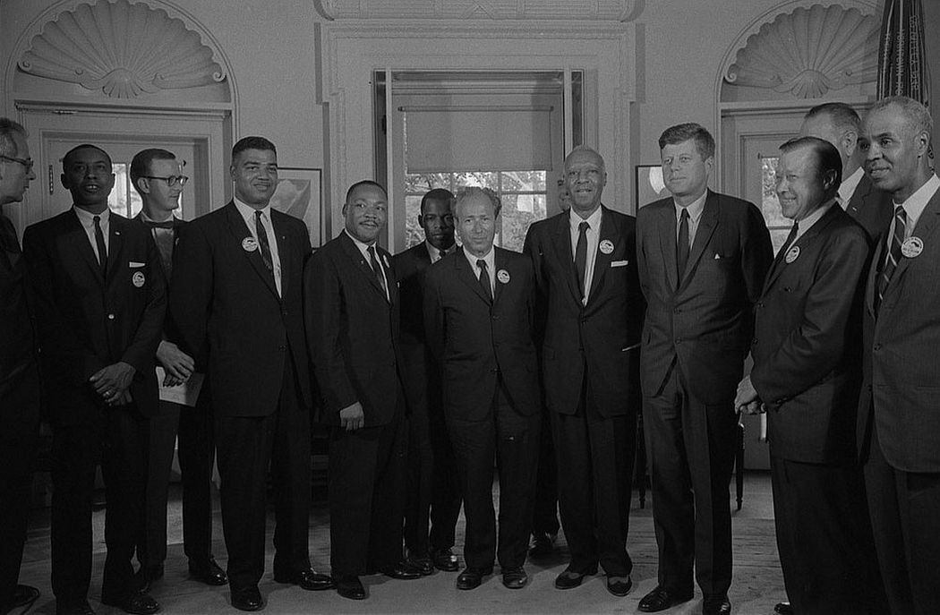 Civil rights leaders meeting with President John F. Kennedy in the Oval Office of the White House following the civil rights march on Washington D.C., August 28, 1963. Pictured are (left to right) Secretary of Labor Willard Wirtz, Congress of Racial Equality leader Floyd McKissick, National Catholic Conference for Interracial Justice leader Mathew Ahmann, National Urban League executive director Whitney Young, Southern Christian Leadership Conference leader Martin Luther King Jr., Student Nonviolent Coordinating Committee chairman John Lewis, American Jewish Congress Rabbi Joachim Prinz, A. Philip Randolph, Reverend Eugene Carson Blake (partially visible), President John F. Kennedy, United Auto Workers president Walter Reuther, Vice President Lyndon Johnson, NAACP executive director Roy Wilkins. (Photo by Reuters/Library of Congress)