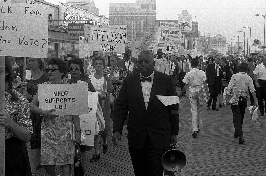 """Marchers, including white Mississippi Freedom Democratic Party supporters, holding signs reading """"Freedom now"""" and """"MFDP supports LBJ"""" while marching on the boardwalk outside the 1964 Democratic National Convention in Atlantic City, New Jersey, August 1964. (Photo by Reuters/Library of Congress)"""