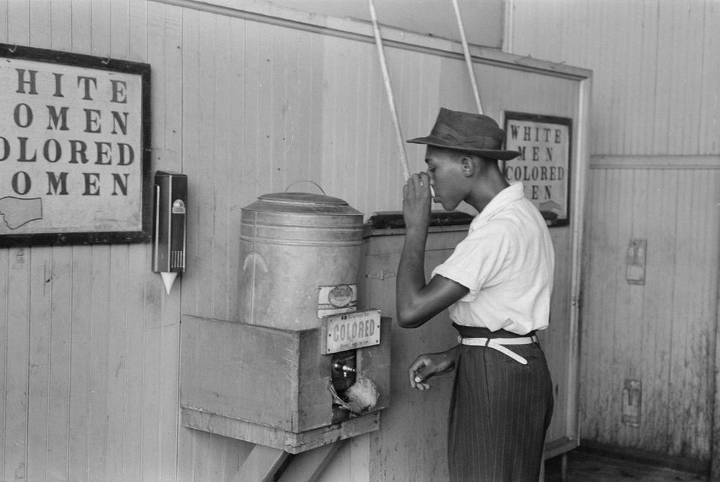 """A man drinks at a """"colored"""" water cooler in a streetcar terminal in Oklahoma City, July 1939. (Photo by Reuters/Library of Congress)"""