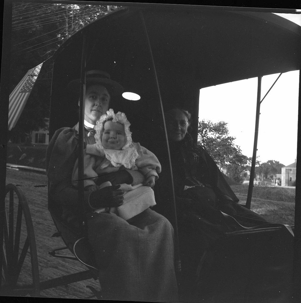 Nellie and baby Theodore in carriage with elderly lady.