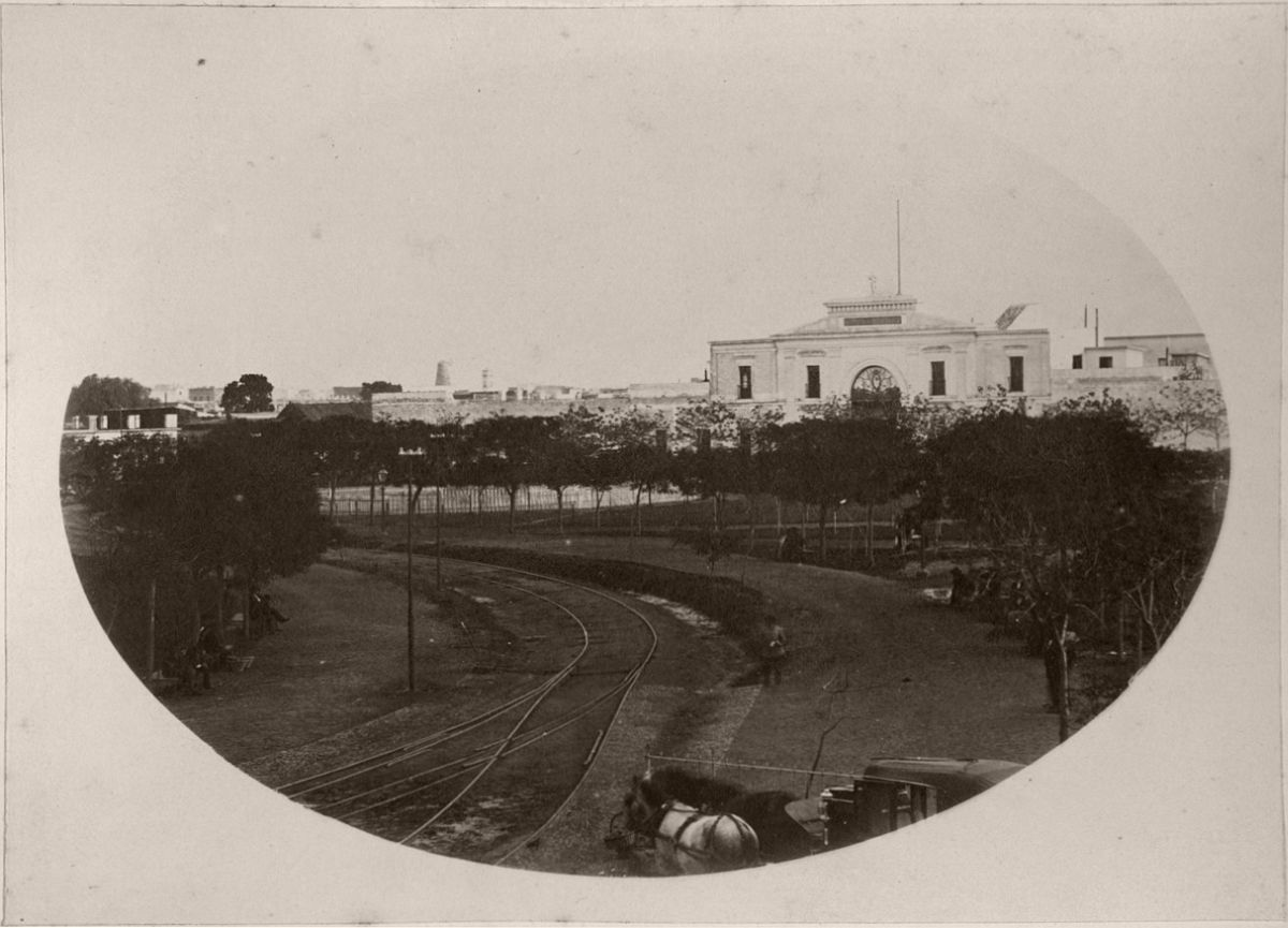 Parque de Artillería Park with its seats, trees and gaslight columns. The photo was taken from the Buenos Aires Western Railway terminus. Rail tracks, a carriage and its horse and the entering to Cuartel de Artillería can be seen in the image.