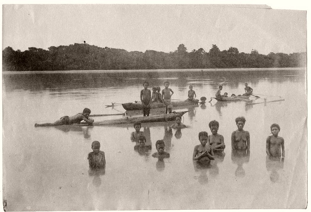 Photograph shows a group of men, women and children standing in a lagoon and on outrigger canoes. Fiji, early 20th century.